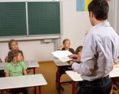Leseförderung in der Grundschule - Lehrer mit Buch in der Hand vor Grundschulklasse