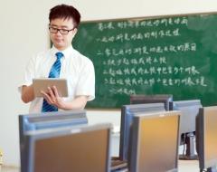 Lehrer mit Laptop in der Hand in Klassenraum